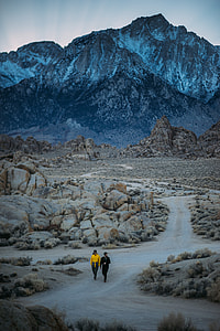 Two person walking on pathway surrounded by rocks