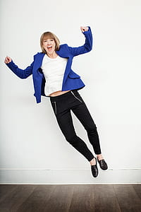 woman jump wearing blue peaked lapel suit jacket and black pants