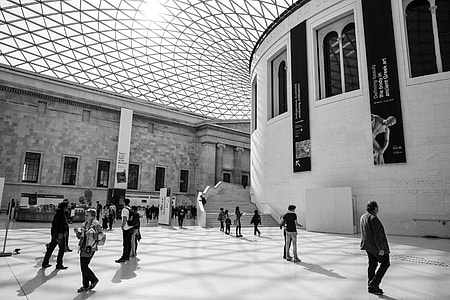 Black and white shot of people enjoying some time in the British Museum in London. This image was captured in the Great Court, this courtyard area was createdby Foster and Partners architects back in the year 2000. The result is a two-acre public space with a wonderful glass roof that is recognised as the largest covered public square in Europe