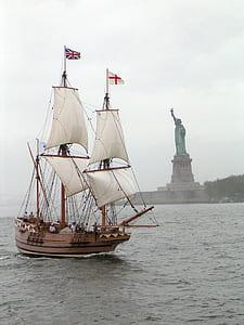 sail ship sailing near Statue of Liberty