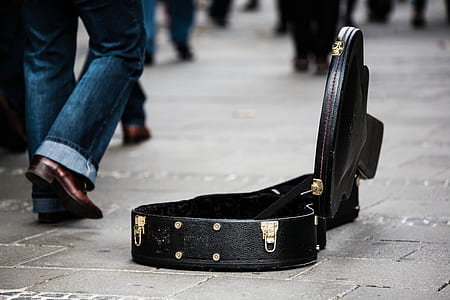 man wearing blue jeans beside the opened black leather guitar case