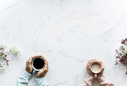 top view of two person feeling coffee cup warmth