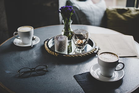 two white ceramic cups on saucers