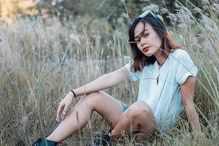woman wearing white shirt and short shorts sitting at grass