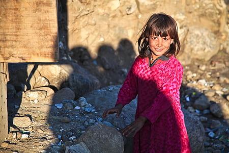 girl wearing pink dress near rocks