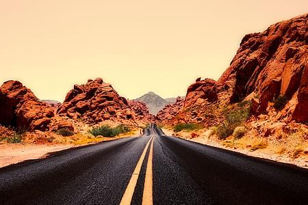black asphalt road beside brown rock mountain