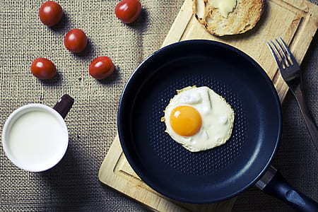 sunny side up on frying pan near stainless steel fork
