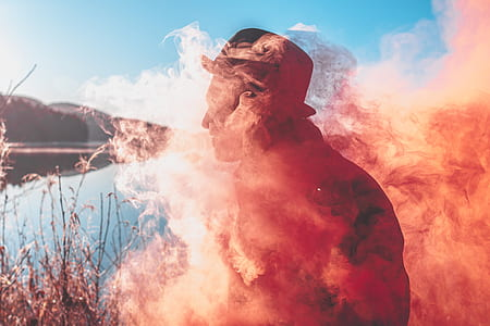 man in hat covered with orange smoke