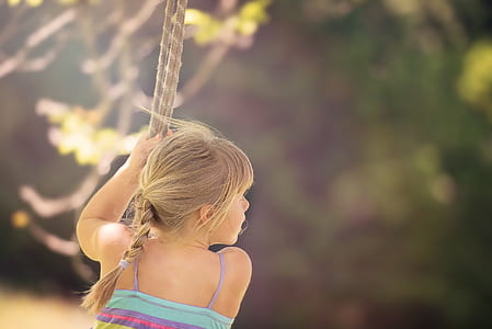 girl playing in swing during daytime