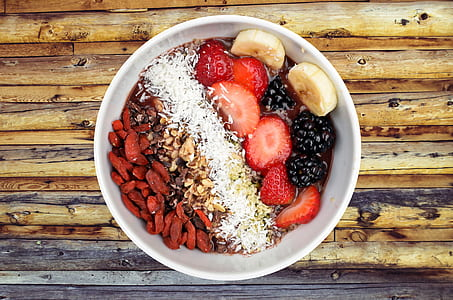 bowl of berries with banana and nuts
