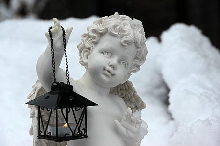 black candle lantern on cherub hand statue