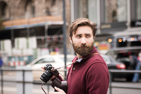 person wearing red collared tops holding black DSLR camera