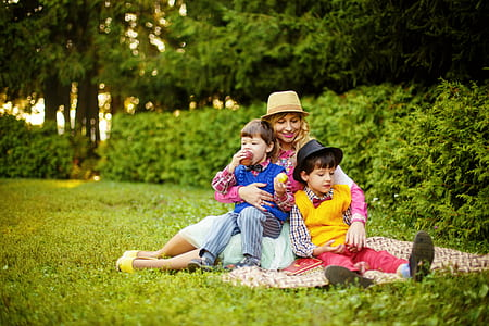 woman hugging her two kids on picnic mat
