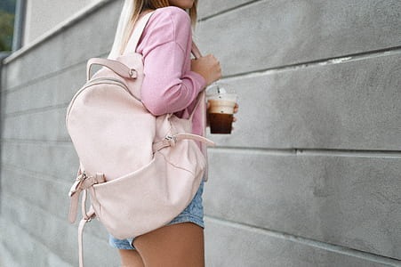 woman wearing pink long-sleeved top with short shorts and backpack