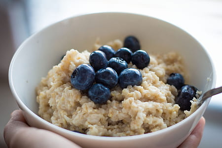 person holding bowl of oats with blue berries