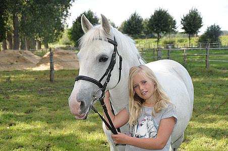 girl holding white horse on green grass field