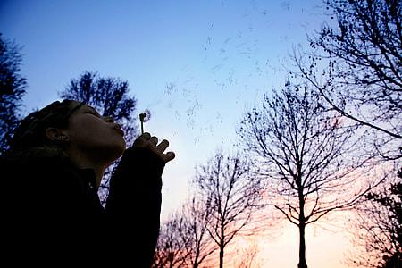 woman blowing bubbles near leafless trees