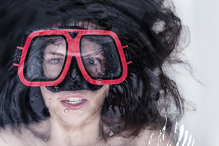 woman lying on water wearing snorkel goggles