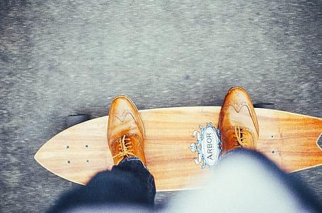 person riding brown Arbor pintail skateboard
