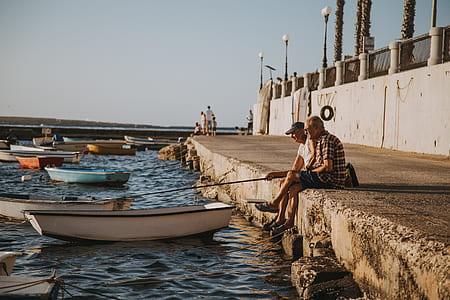 two men sitting on pavement fishing on sea