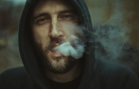 man in black hoodie releasing smoke through mouth