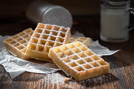 four waffle on white textile near mug