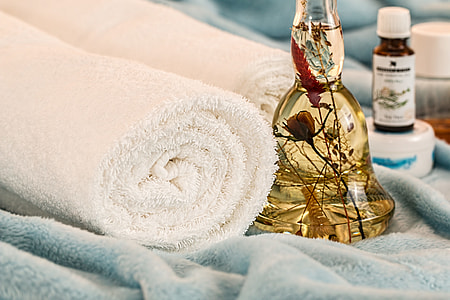 two white bath towels and clear glass bottle