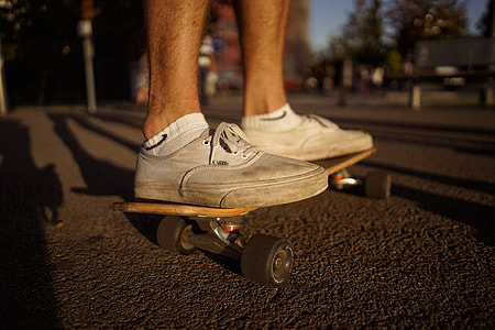 person wearing white Vans Authentic riding skateboard