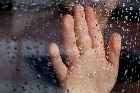 human hand touching glass panel with water moist