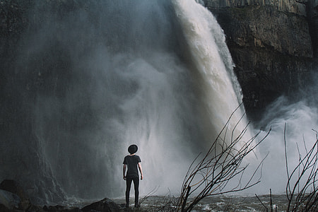 boy standing near waterfalls