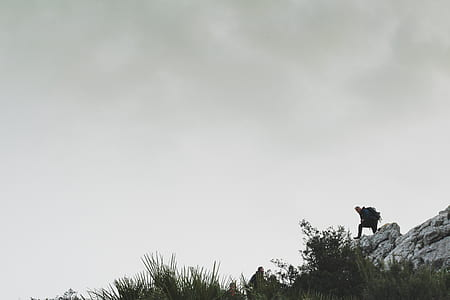 Person on Rocky Mountain Under White Cloudy Sky