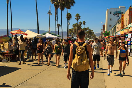 man carrying yellow backpack in front of pathway during daytime
