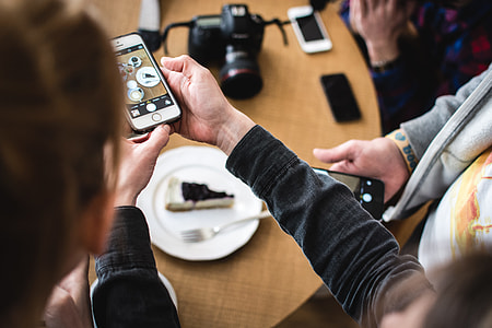 Girl shooting cake with her iPhone