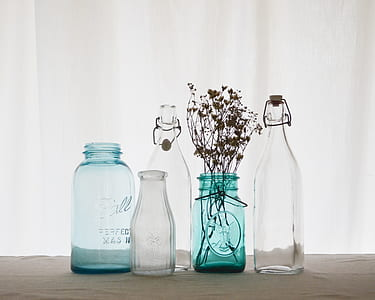 four clear and blue glass bottles