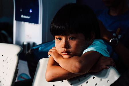 boy leaning on white chair back