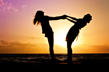 silhouette of two woman holding each other during dusk