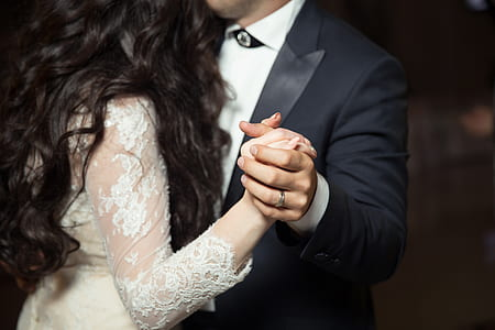 man wearing black peak lapel suit jacket and woman wearing white lace long-sleeved dress holding hands while dancing