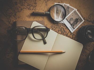 brown pencil and black framed eyeglasses