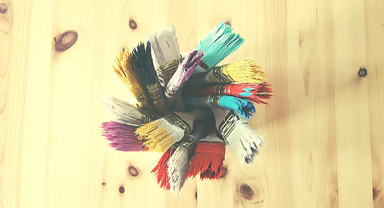 assorted-color paint brushes on beige table