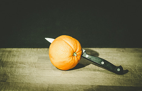 black kitchen knife beside orange