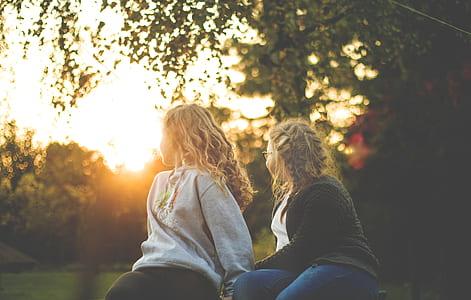 Two Women Sitting Near Green Tree during Sunset