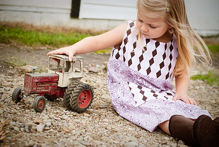 girl in white and purple sleeveless dress playing red and white toy car at daytime