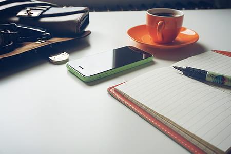 green iPhone 5c beside orange ceramic teacup and saucer