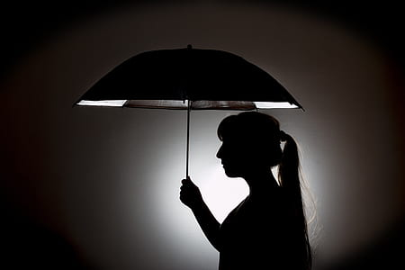 silhouette of woman holding umbrella