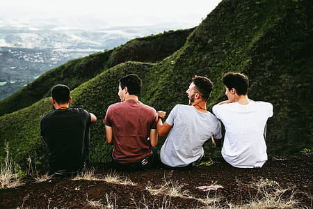 four men sitting on brown ground photo during daytime