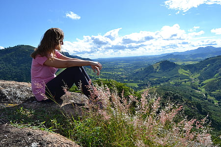 woman wearing pink t-shirt sitting above the mountain