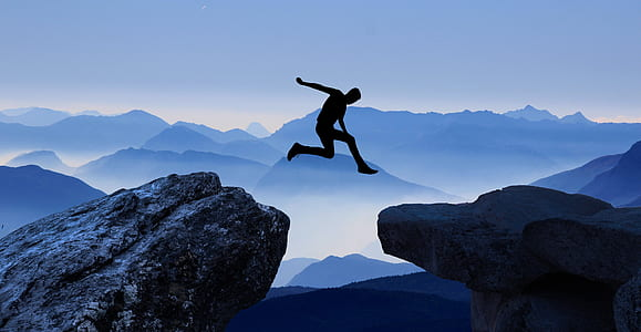 man jump from tip of mountain to another mountain