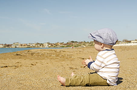 baby in white and brown striped long-sleeved shirt and pants outfit sitting on brown sand at daytime