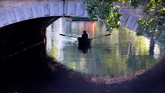 person riding paddle boat under bridge