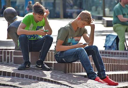 two man sitting holding phone